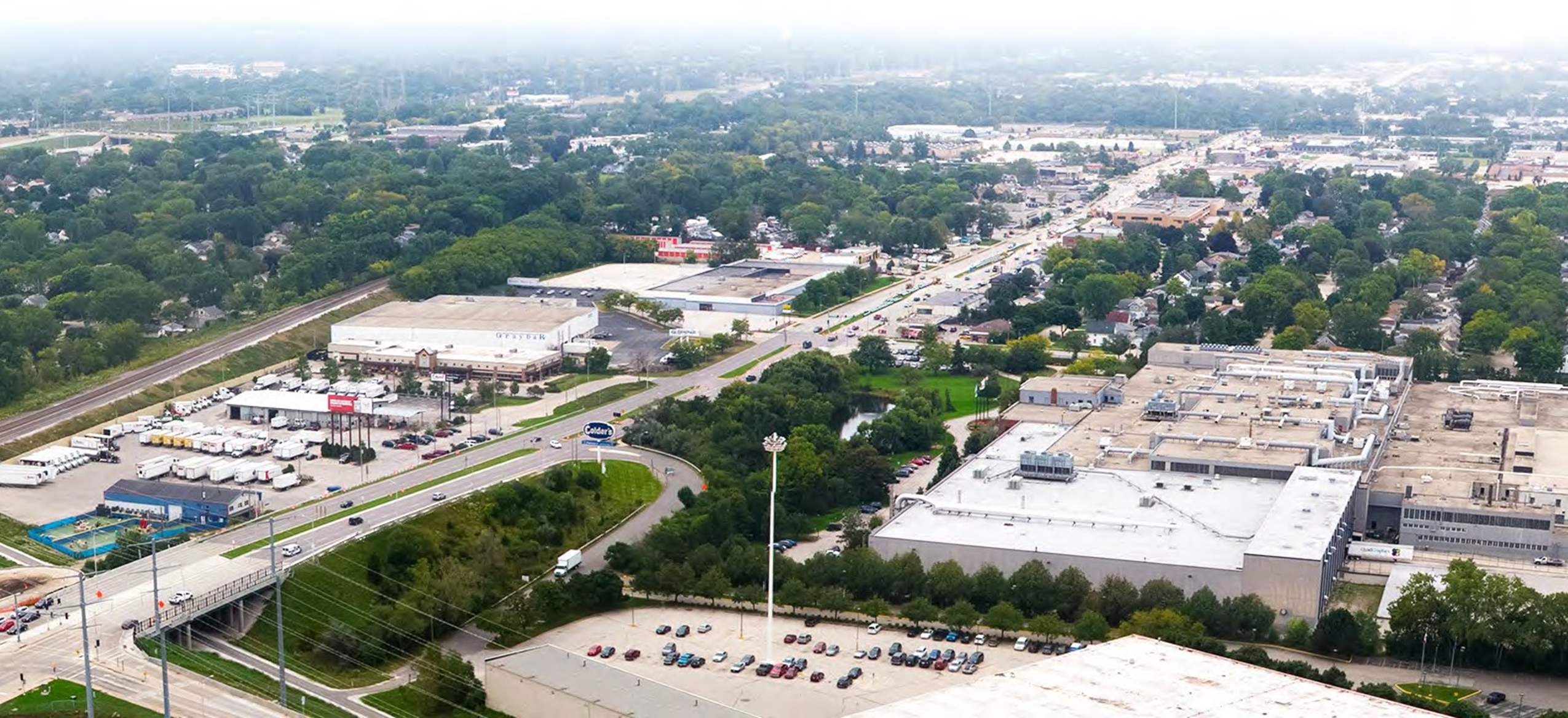 Aerial photograph of Hwy 100 showing buildings, street, and parking lots