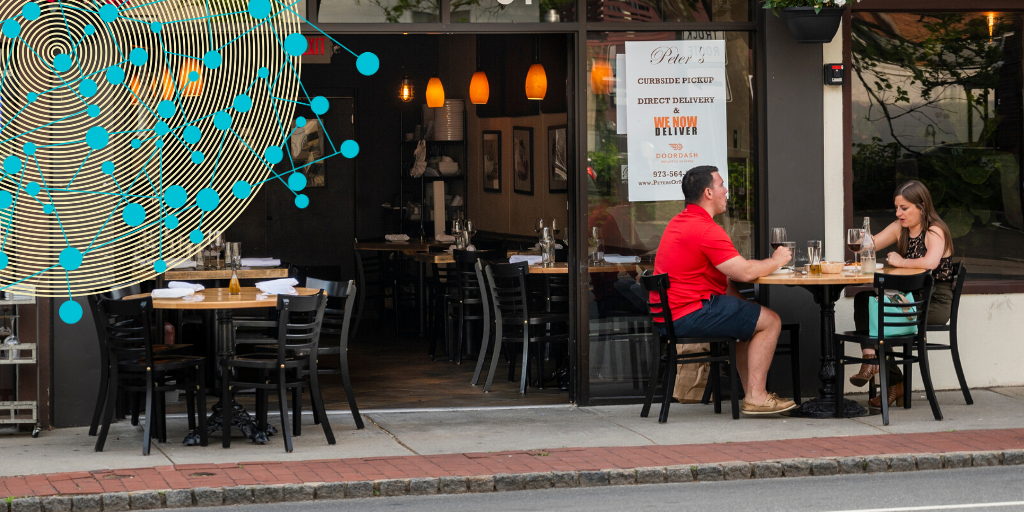 Photograph of couple at outdoor table on sidewalk in front of restaurant